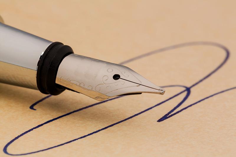 Eine Unterschrift Und Ein Füllhalter Auf Gelben Papier. Symbolfoto Für Vertrag, Testament Und Grafologie